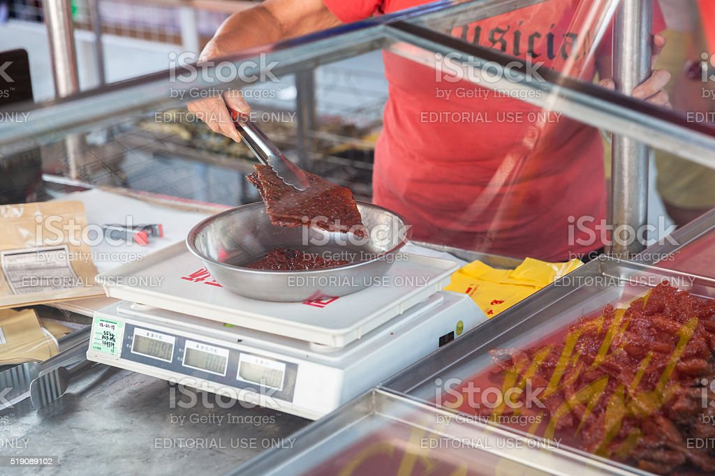 Woman weigh Chinese dried pork stock photo
