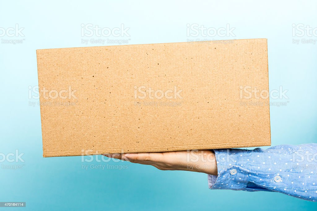 Woman weighing a cardboard box with her hand. stock photo