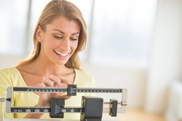 woman weighing herself on balance scale - scale stock photos and pictures