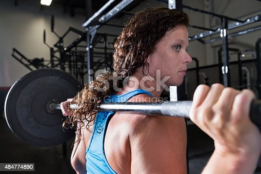 A woman lifts free weights in a professional gym.  She lifts the barbell behind her head to exercise and build the muscles in her back and shoulders.  The lighting is dramatic.