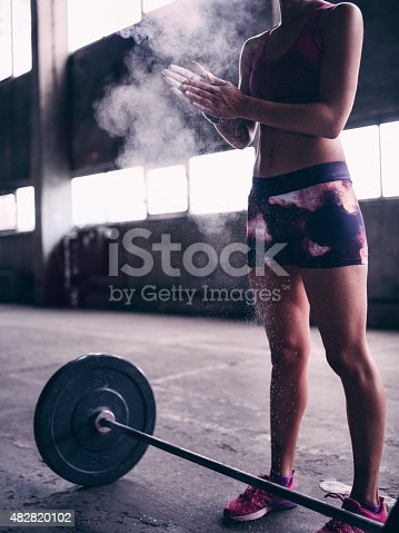istock Woman weight-lifter clapping powder from her hands 482820102