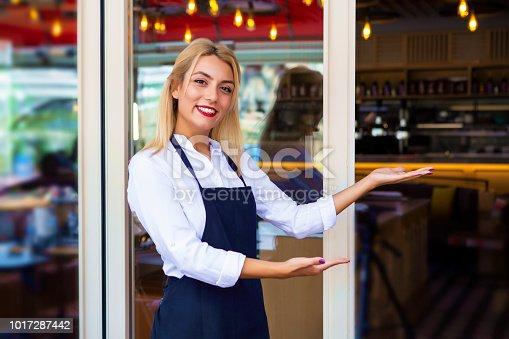 1066358064istockphoto Woman welcoming customers to her restaurant 1017287442