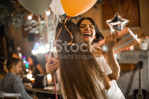Woman welcoming guest on her birthday dinner party and receiving gifts