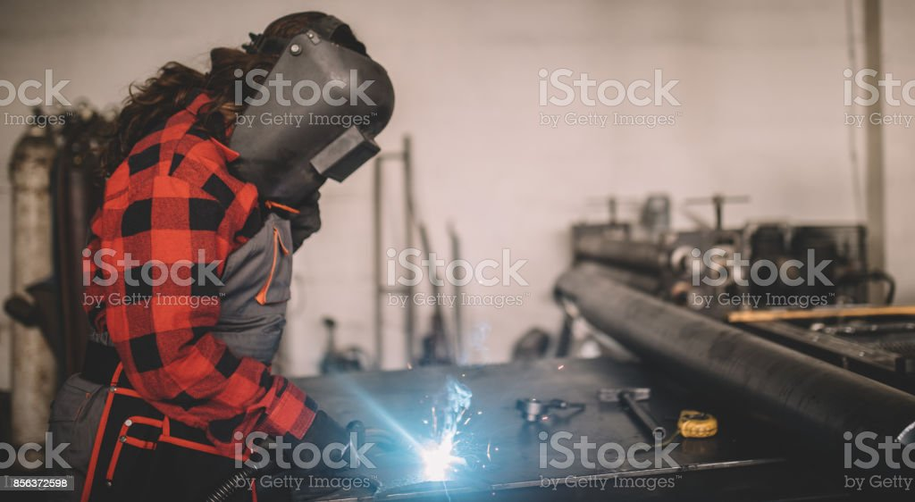 One woman, young adult welding in workshop.