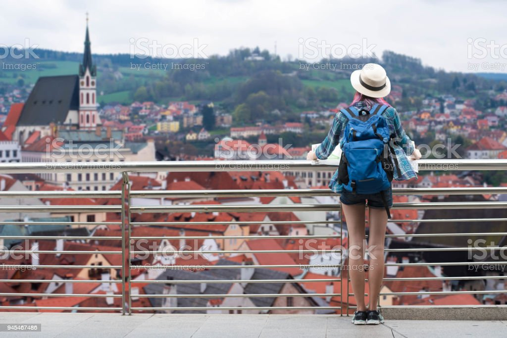 Woman westerner travel in backpack with map looking at city view of Český Krumlov Town in the Czech Republic stock photo
