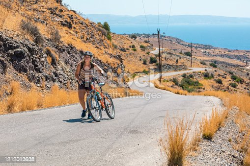 Women wheeling bicycle along country road, vacation, healthy lifestyle. taking a break