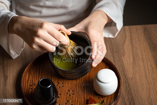 Woman whisking matcha powder while making matcha green tea drink with traditional Japanese accessories for tea ceremony