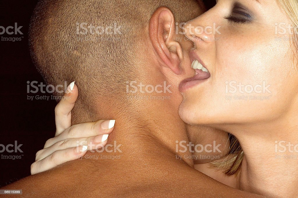 Woman whispering in mans ear stock photo