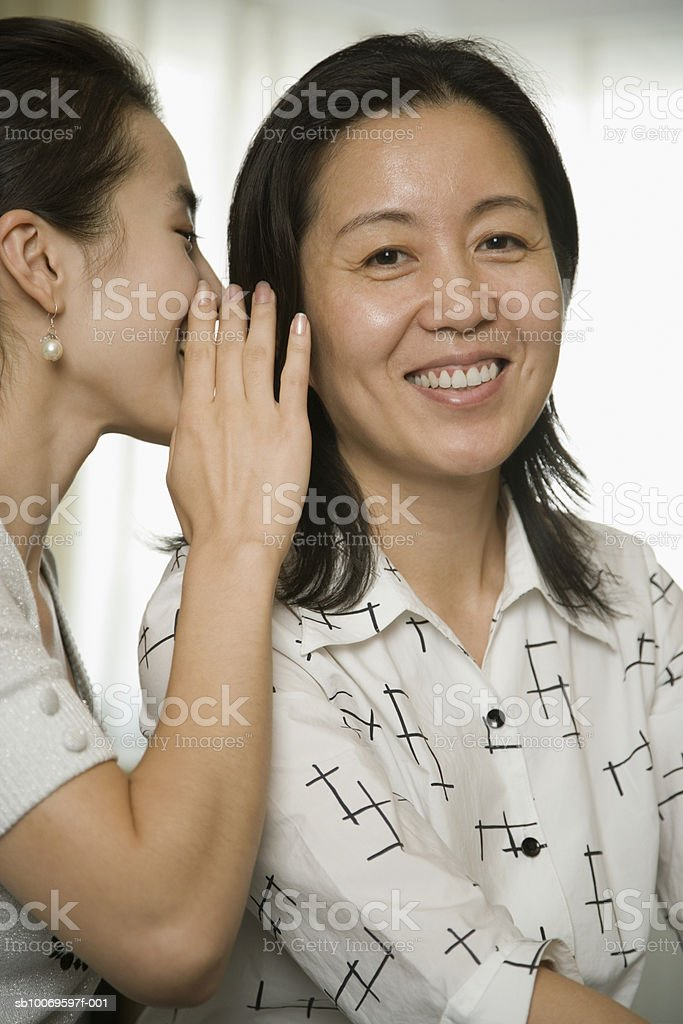 Woman whispering in mature woman's ear royalty-free stock photo