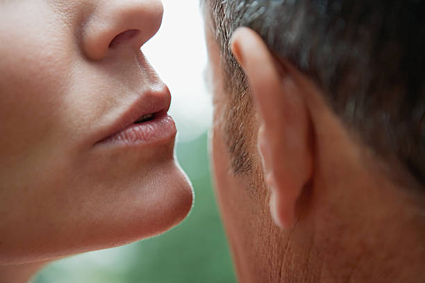 Woman whispering into man's ear  human ear stock pictures, royalty-free photos & images