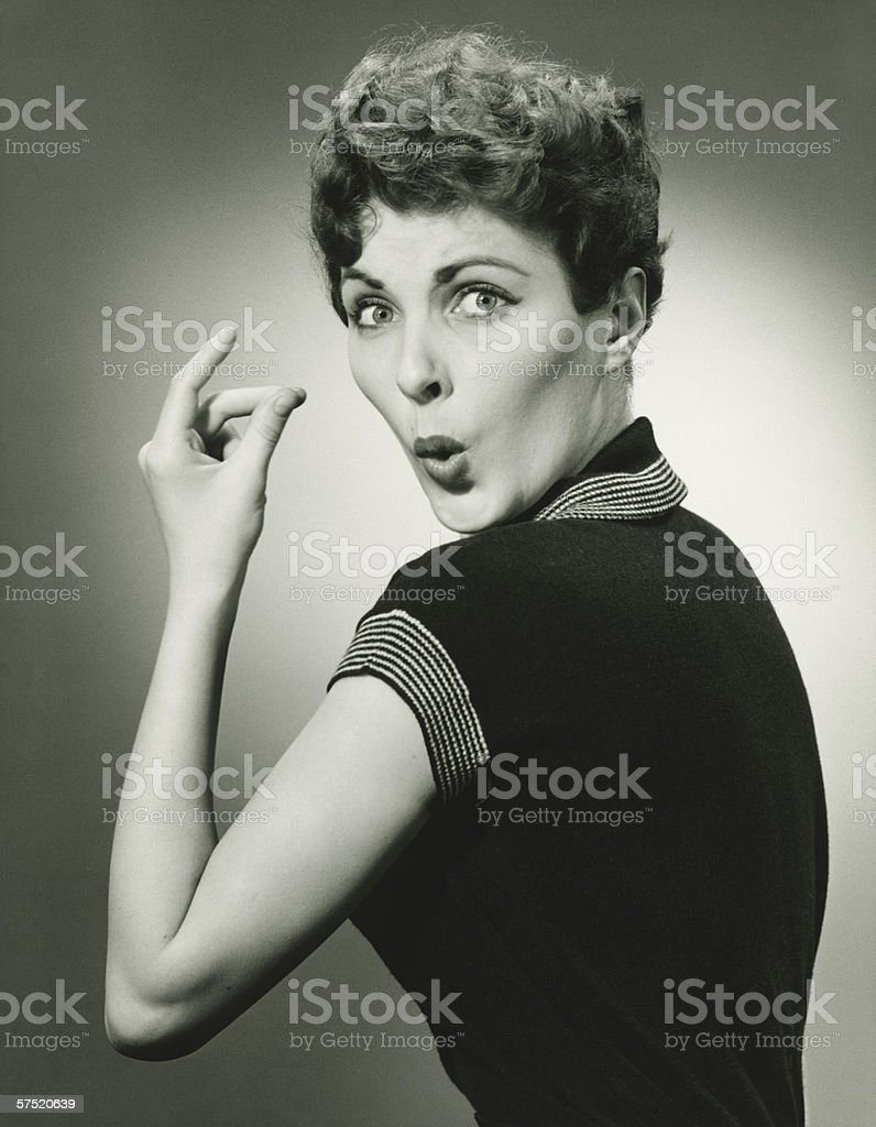Woman whistling and snapping fingers in studio, (B&W), portrait stock photo