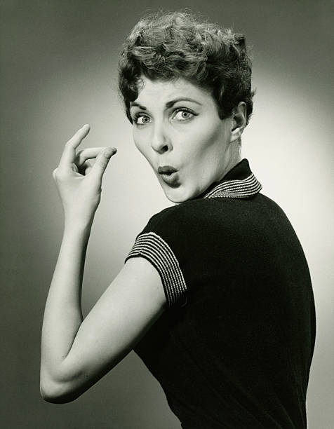 Woman whistling and snapping fingers in studio, (B&W), portrait  snapping stock pictures, royalty-free photos & images
