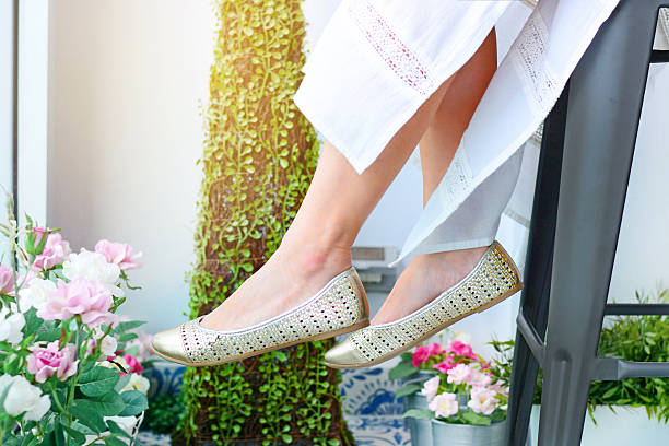 woman white dress and gold casual shoes stock photo