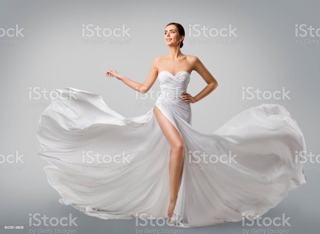 Woman White Dress, Fashion Model Bride in Long Silk Wedding Gown, Elegant Flying Fabric, Fluttering Cloth stock photo