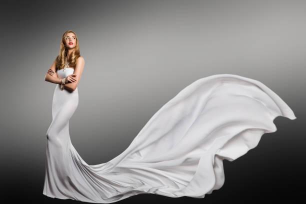 frau weißes kleid, mode-modell in lange seide sexy kleid, winken schweif fliegen stoff zug, flattern tuch - lange abendkleider stock-fotos und bilder