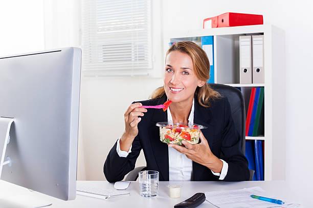 femme qui mange en travaillant stock photo