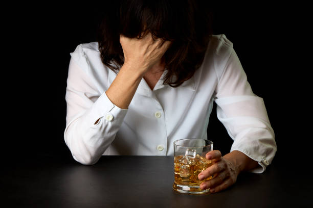 Woman who has abused alcohol with a glass of Scotch and ice stock photo