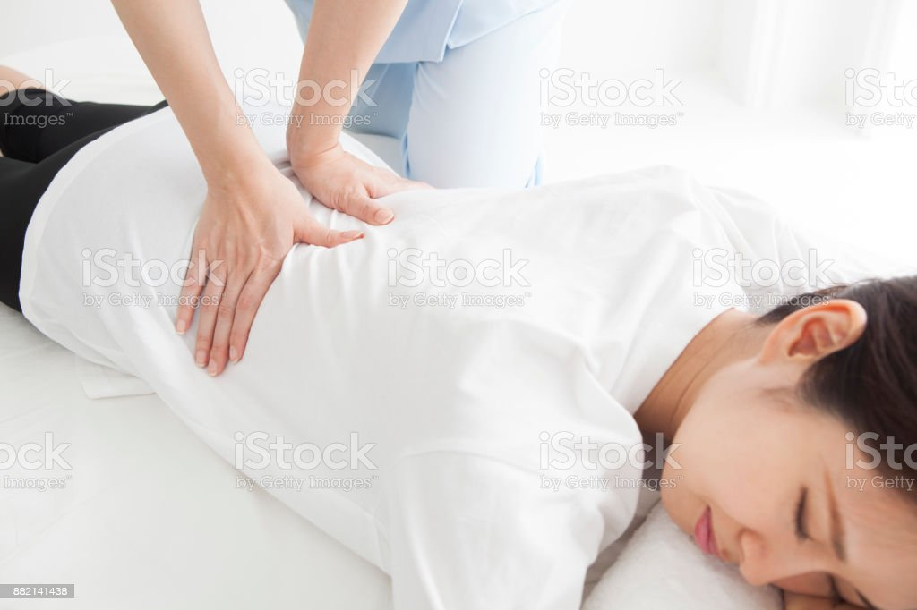 A woman who has undergone waist surgery lying on her face. stock photo