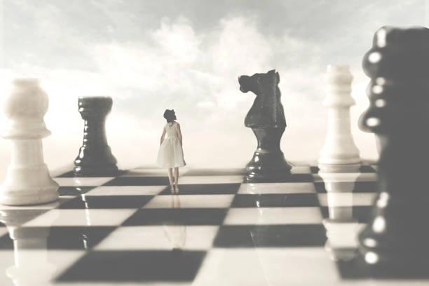 Frau, die mit den weißen Schachborads verbündet ist, schaut misstrauisch auf ihren schwarzen Rivalen; Konzept der Strategie – Foto