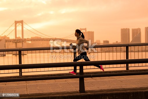 A woman is running across the city.