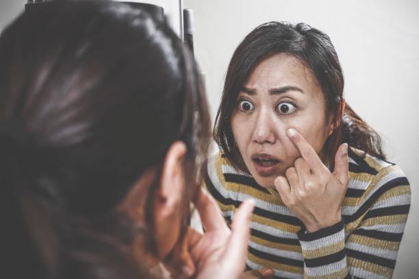 鏡を見てショックを受けた女性 ストックフォト