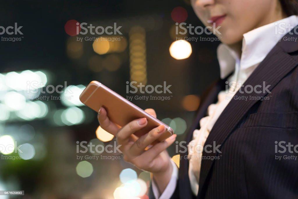 帰宅しながら携帯電話を運営している女性 ストックフォト