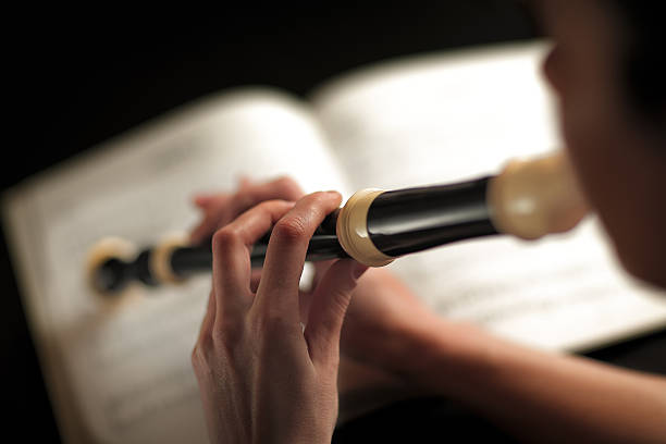 woman who plays the flute - recorder stock photos and pictures