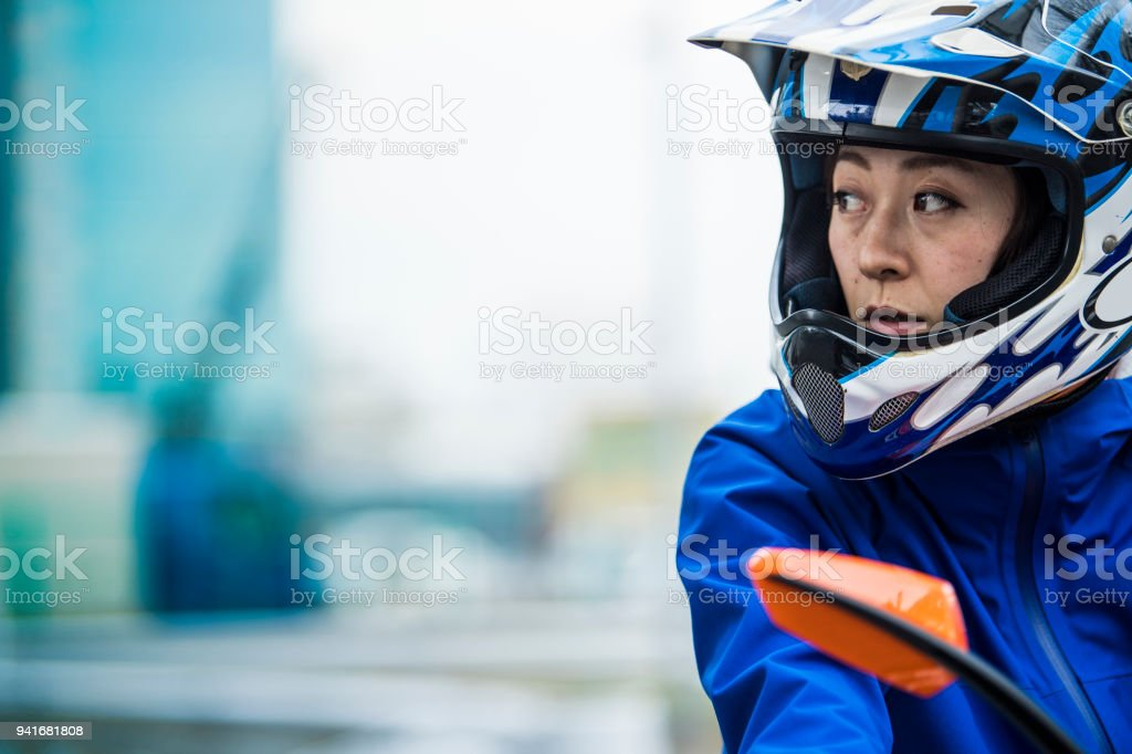 A woman who stops the bike and looks somewhere. stock photo