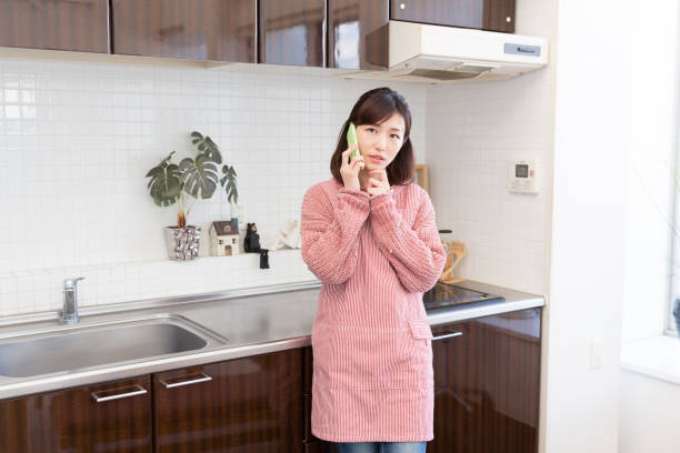 woman who talks on the telephone in a kitchen - stay at home parent stock pictures, royalty-free photos & images