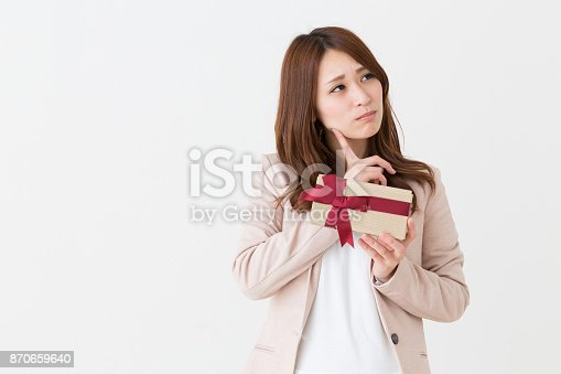 istock woman who thinks while having a present 870659640