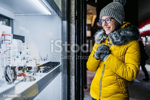 Young woman looking through Jewelry store window at night.