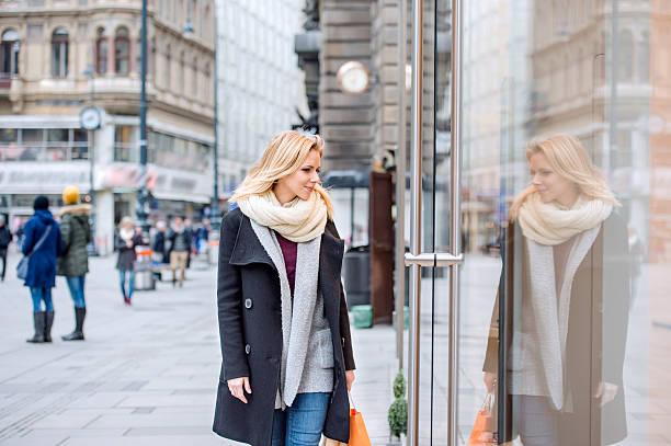 woman window shopping in centre of the city. winter - wintermantel damen wolle stock-fotos und bilder