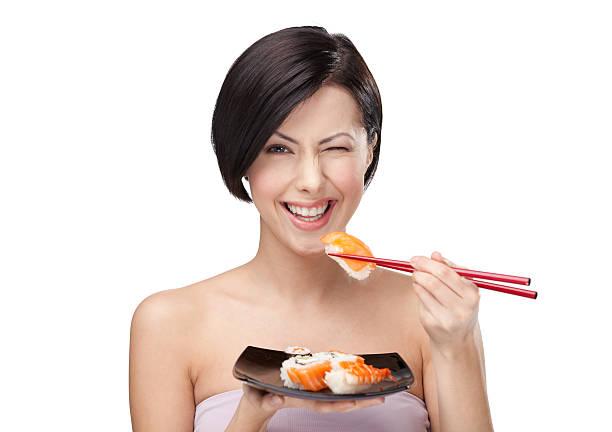 schöne frau essen sushi - sushi essen stock-fotos und bilder