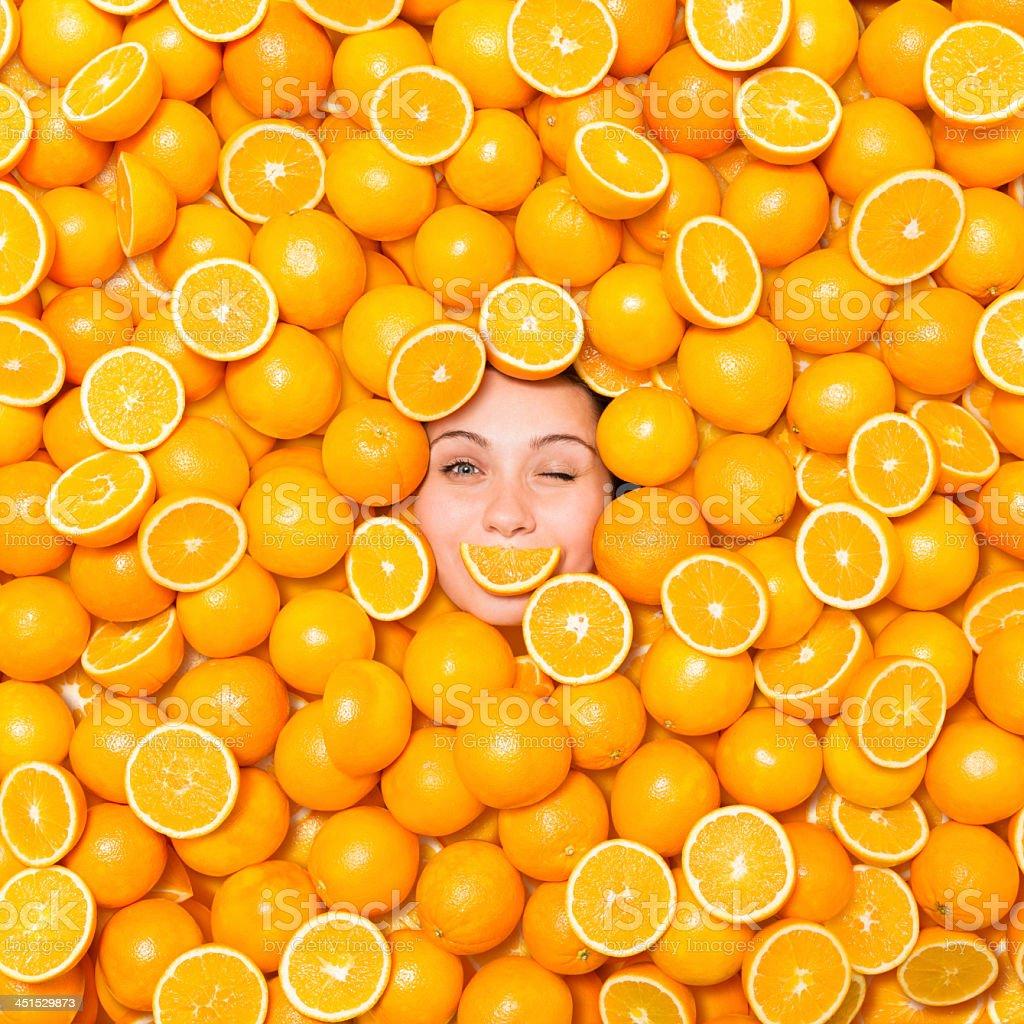 Donna Fare l'occhiolino circondato con arance - foto stock