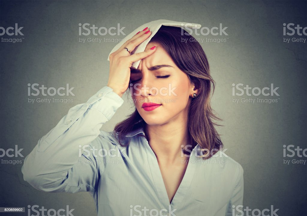 woman wipes sweat from her forehead with a handkerchief stock photo