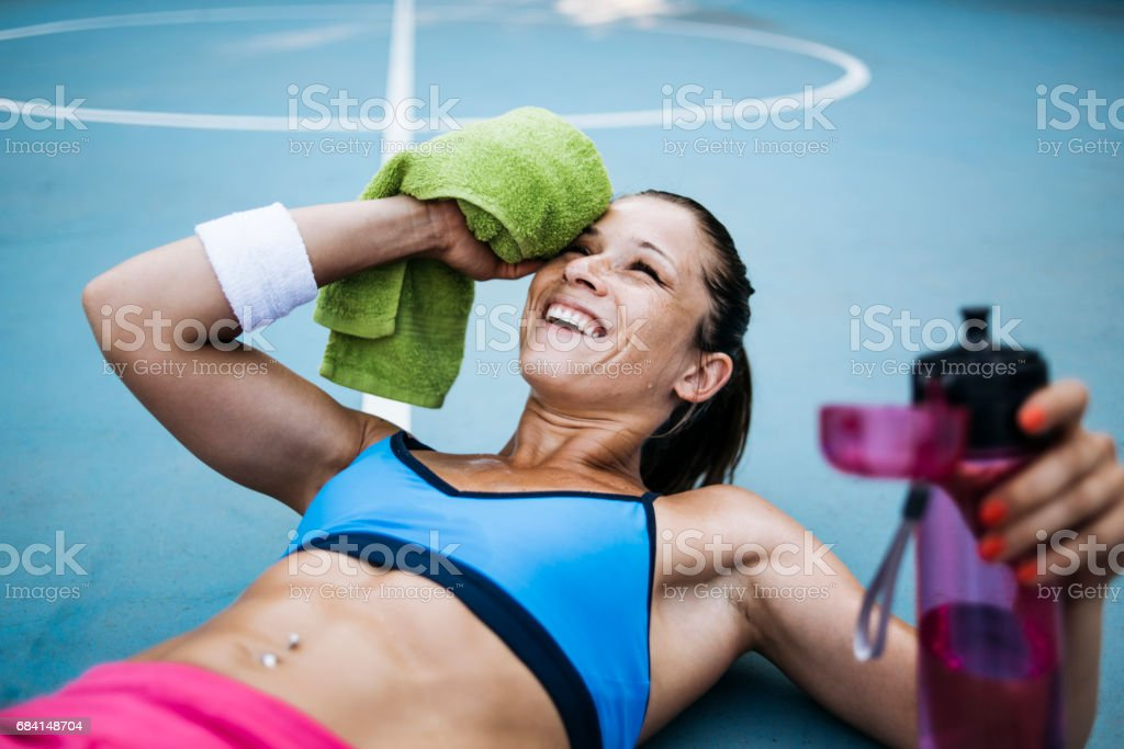 女性は、彼女の顔を離れて汗を拭く ロイヤリティフリーストックフォト