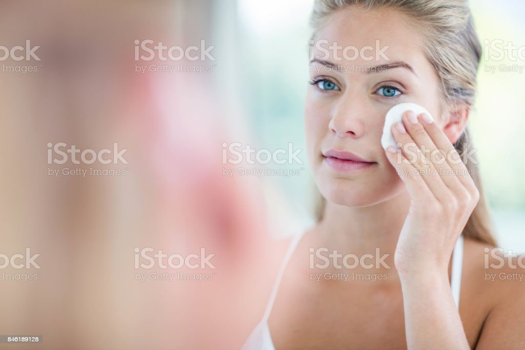 Woman wiping her face with cotton pad stock photo