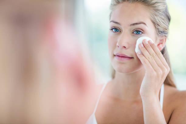 femme essuyant son visage avec une serviette en coton - démaquillant photos et images de collection