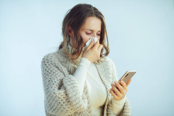 woman wiping nose with napkin ordering pills in online shop stock photo