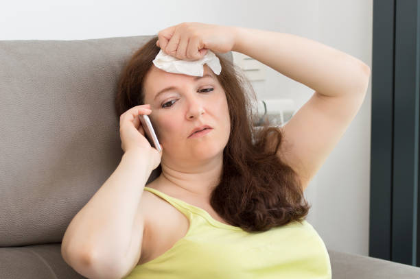 Woman wiping off sweat from forehead and calling the customer service stock photo