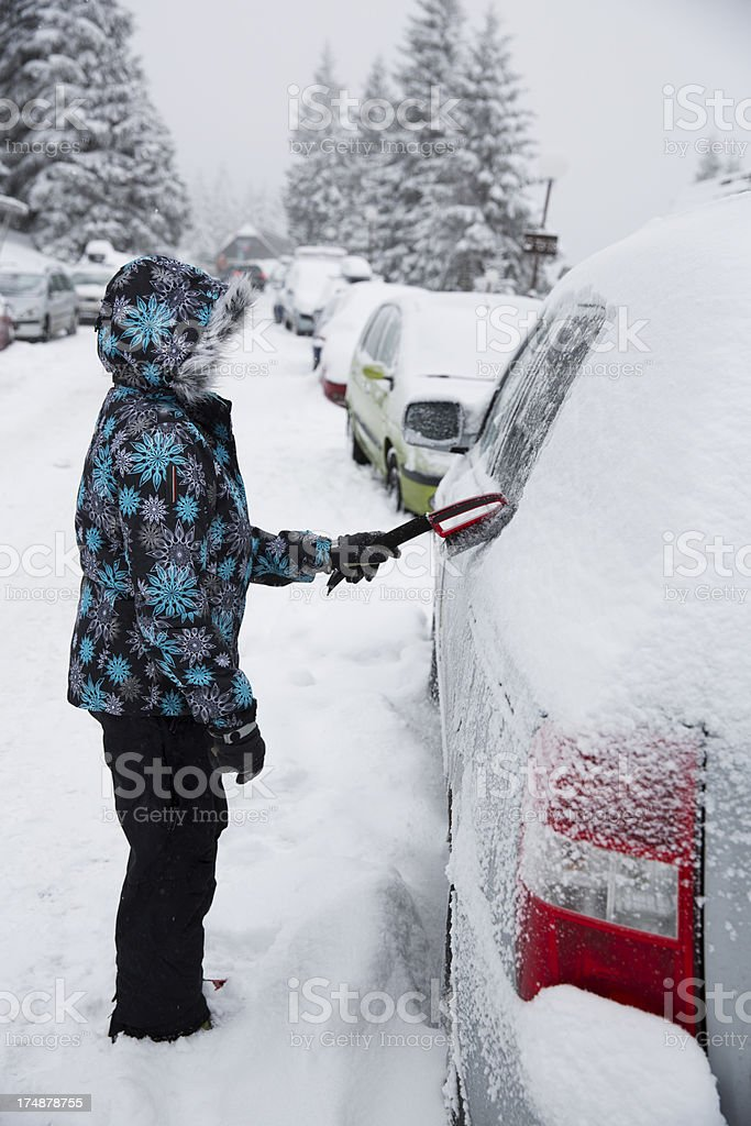 Woman wiping snow from her car royalty-free stock photo