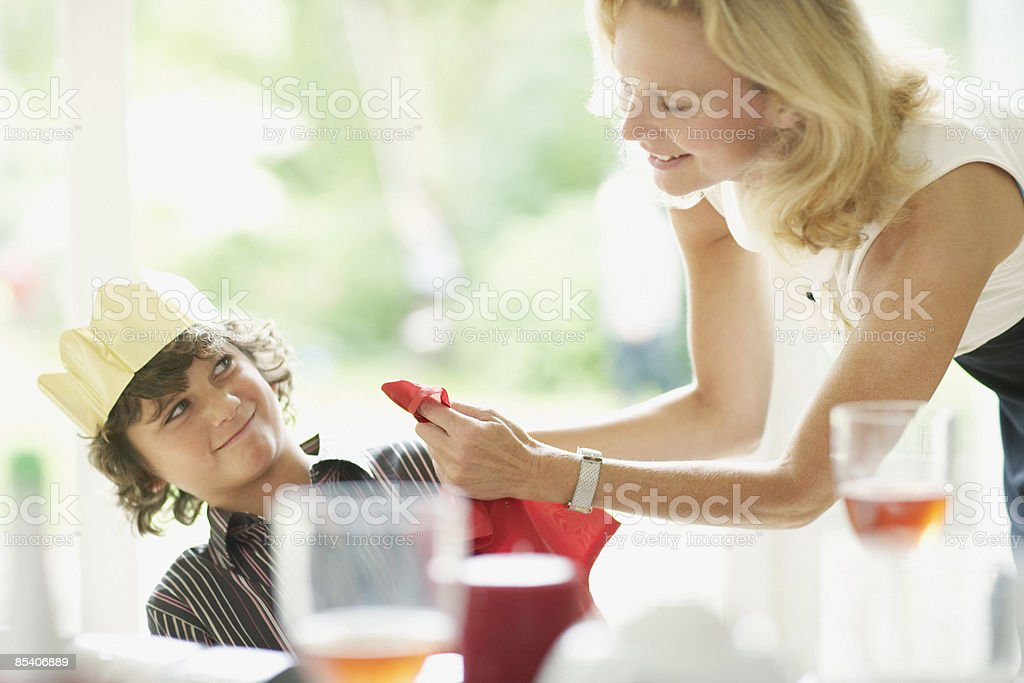 Woman wiping sons face during Christmas dinner royalty-free stock photo