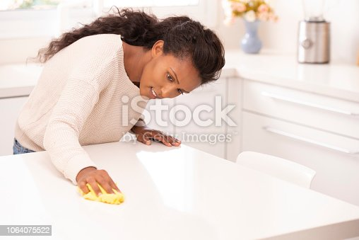 Housewife wiping the marble table with a microfiber cloth at home kitchen. The domestic woman cleaning at home. The household, housekeeping concept.
