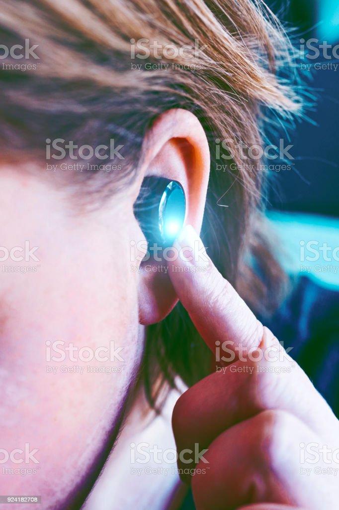 Mulher sem fio fones de ouvido e controlá-los pressionando um botão - foto de acervo