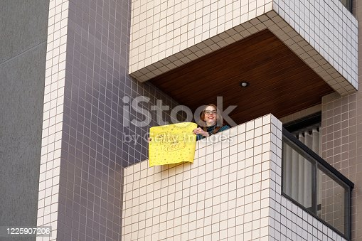 Woman wishing Happy Valentine's Day holding sign.
