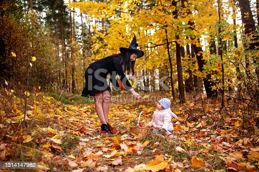 woman witch plays with a small child in the autumn forest. halloween concept costumes. witch and bunny. concept of friends mother and daughter