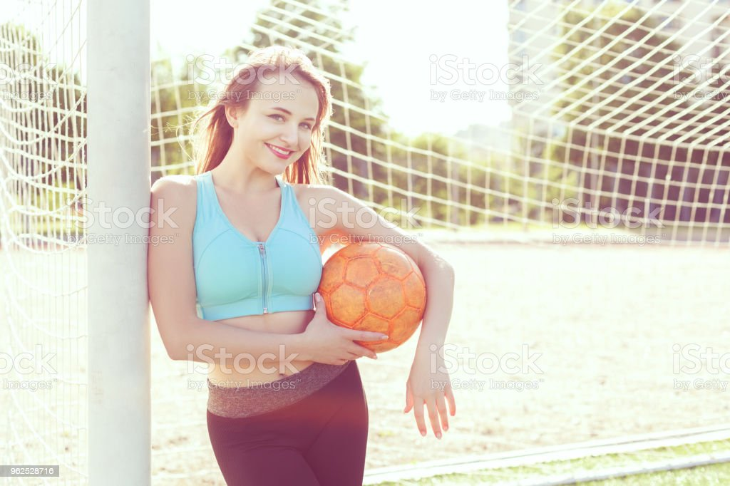 Woman with a ball at the gate. - Royalty-free Activity Stock Photo