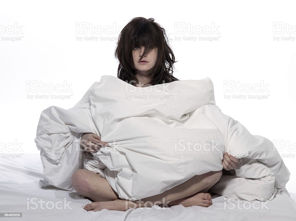 A woman with a bed head wrapped in duvet royalty-free stock photo