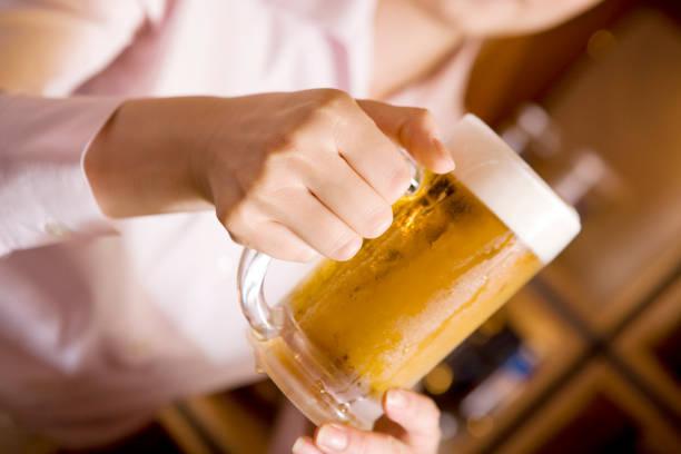Mujer con una cerveza en la mano - foto de stock