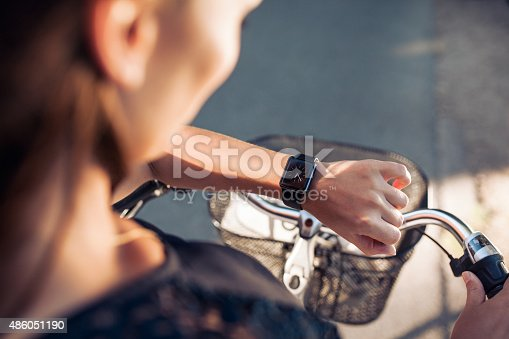 istock Woman with a bicycle looking at her smartwatch 486051190